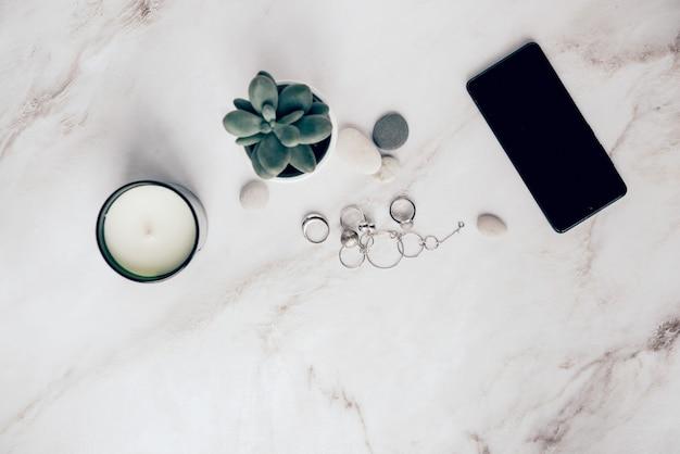 Домашний декор и женские аксессуары плоские лежат смартфон сочные и серебряные украшения на каменном столе