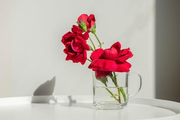 Домашний декор, интерьер. красивые красные розы в стеклянной чашке на белом столе