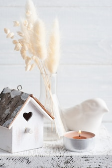 Home decor in scandinavian style with pampas grass dry flowers on rustic wall in monochrome style. scented candles and birdhouse with copy space