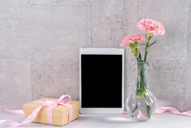 테이블 벽 옆에 사진 프레임으로 피는 카네이션과 태블릿이있는 가정 장식