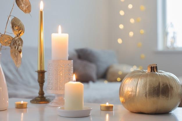 Домашний декор с золотой тыквой и зажженными свечами