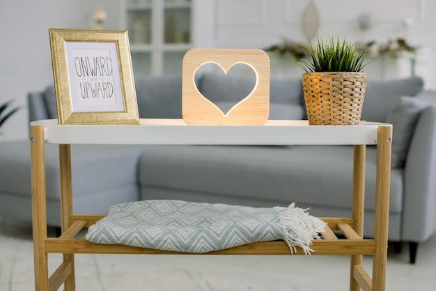 가정 장식, 나무 램프 및 아늑한 액세서리. 사진 프레임이있는 작은 테이블, 하트 그림이있는 장식용 나무 램프 및 녹색 식물의 전면보기