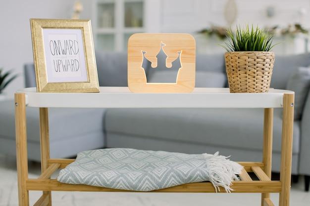 가정 장식, 나무 램프. 사진 프레임이있는 작은 테이블, 성 타워 그림이있는 장식용 나무 램프 및 고리 버들 꽃 냄비에 녹색 식물의 전면 뷰.