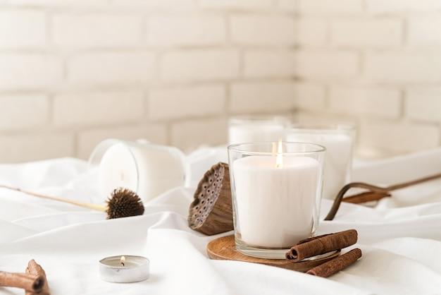 Украшение дома и интерьер. красивые горящие свечи с корицей и сухими цветами на белой поверхности ткани