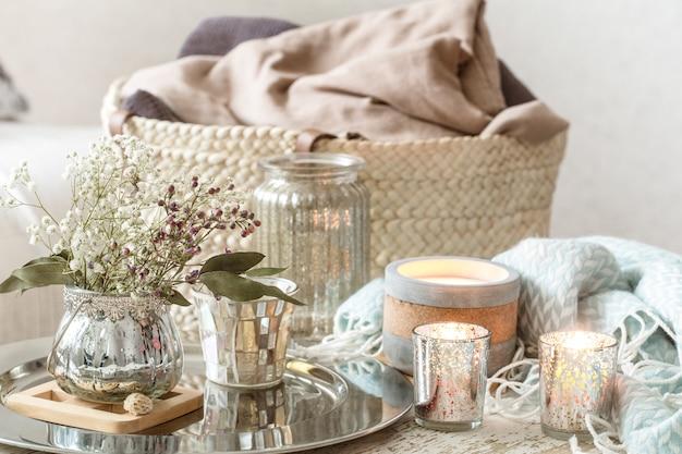 インテリアの家の装飾。ターコイズブルーの毛布と籐製のバスケットに花瓶とキャンドルの花瓶