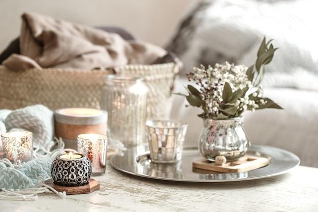 インテリアの家の装飾。花とキャンドルの花瓶とターコイズブルーの毛布と枝編み細工品バスケット