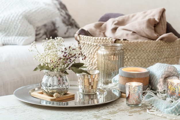 Home decorations in the interior. turquoise blanket and wicker basket with a vase of flowers and candles