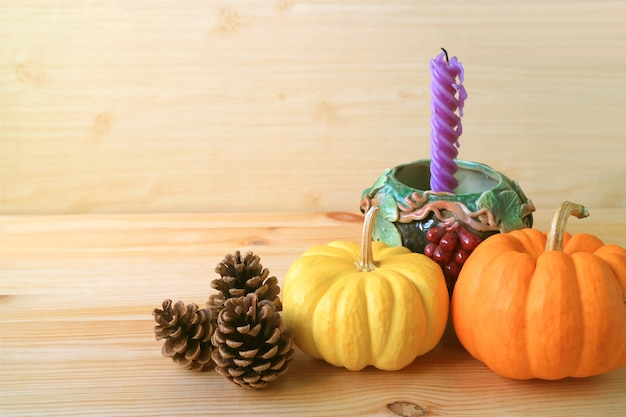 Home decorations with vibrant pumpkins, natural pine cones and purple candle in grape motif holder