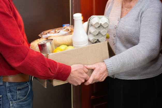 Home delivering food or donation box to senior citizens in quarantine during covid-19