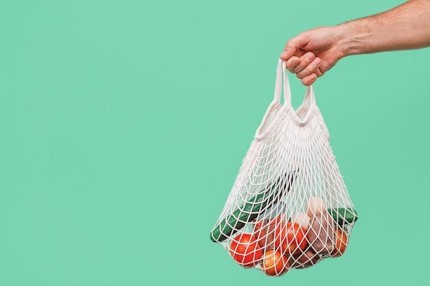 Домой с доставкой некоторых продуктов. рука человека, делающего хозяйственную сумку в парадной двери.
