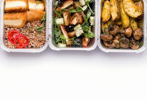 Концепция доставки на дом. контейнеры вегетарианской еды, гречки, картофеля, грибов и салата