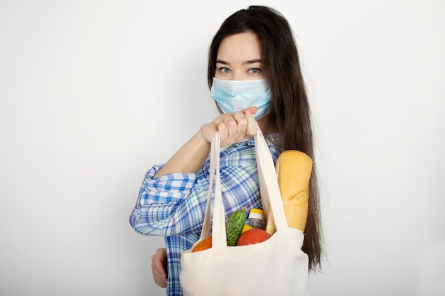 Home delivery during coronavirus, viral outbreaks, and pandemics. girl in blue gloves holds a bag with products on a white isolated background. covid-19