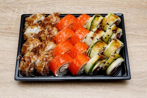 Доставка на дом набора суши в пластиковом ящике.
