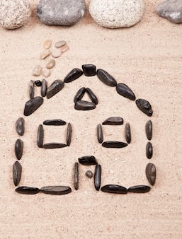 Home designed with pebbles on the sand of a beach