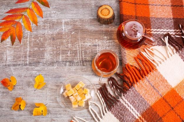 체크 무늬 오렌지 체크 무늬와 찻잔 가을 잎이 있는 홈 데스크 테이블