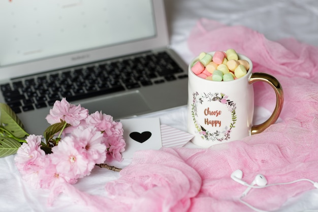 Home desk with laptop, headphones and cup of coffee with marshmallows