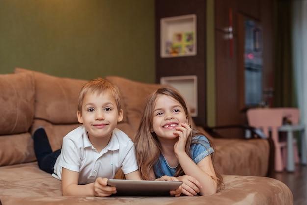自宅での家庭用遠隔学習。双子の兄と妹は、タブレットを使用して自宅で勉強しています。彼らはソファに横たわっている間幸せで笑っています