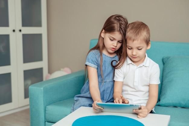 自宅での家庭用遠隔学習。タブレットを使用して自宅で勉強する双子の兄と妹