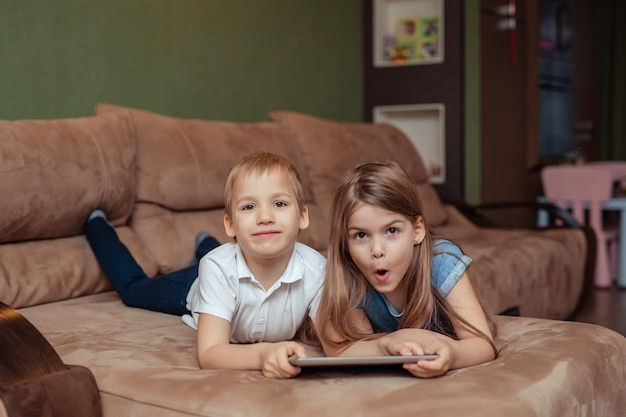 Home distance learning at home. twins brother and sister are studying at home using a tablet. they are happy and laughing while lying on the couch