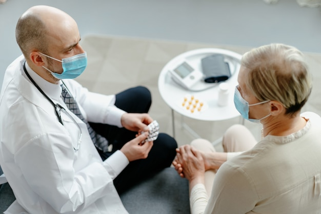 Home doctor explains to the patient the rules for taking medications Premium Photo