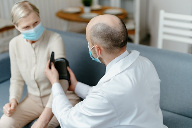 Home doctor is measuring the pressure of his patient