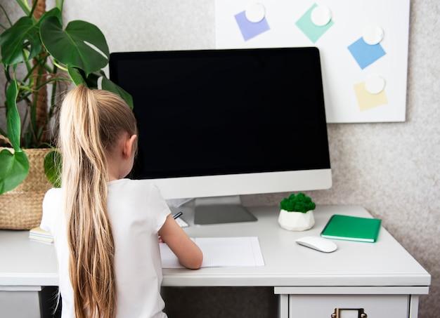 家庭教育。自宅の机で働く女の子
