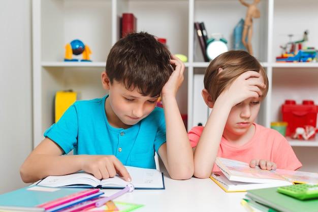가정 교육, 홈 스쿨링. 피곤한 아이들은 테이블에서 책을 읽고 있습니다. 두 명의 학생이 어려운 과제와 책 읽기로 스트레스를 받았습니다. 남학생들은 숙제를 하느라 고생하고 있습니다.