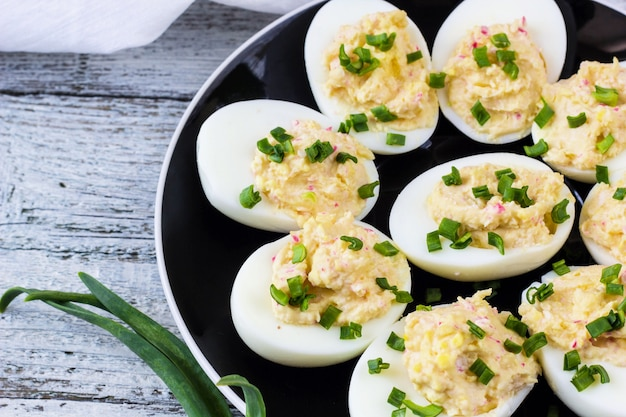 Home eggs stuffed with cheese and crab topped with green onions