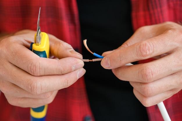 家庭用電気技師は、引き込み式ナイフのクローズアップ、技術と電子機器の概念を備えた延長プラグコードケーブルワイヤーを修正します