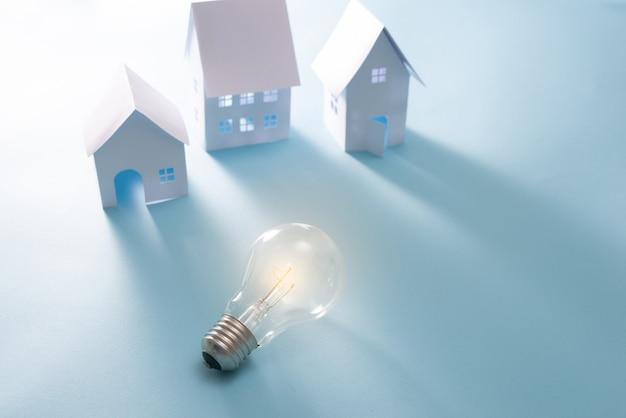 青い背景の上の電球とホームエネルギー