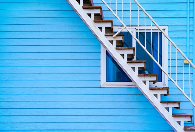 Home exterior design - blue wooden house's wall and stairs to upper floor