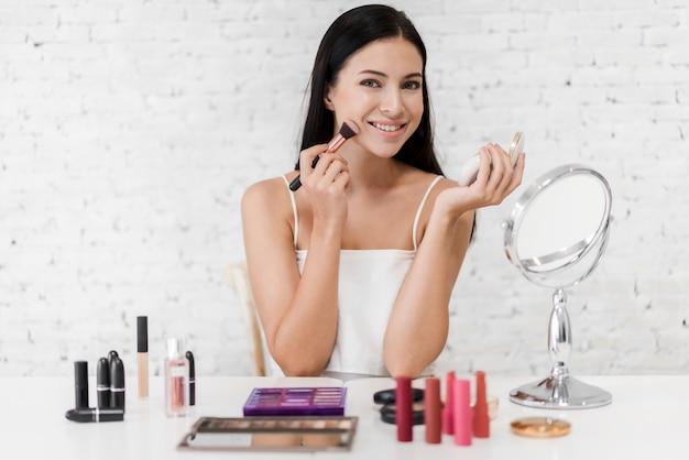 化粧品セットhome.facialの美しさと化粧品のコンセプトで化粧ブラシを保持している若い美しい女性新鮮な健康的な肌を笑顔