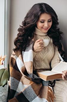 Домашняя праздничная атмосфера. пить чай, сидя в кресле с вязаным пледом у камина. очаровательная женщина с большой улыбкой.