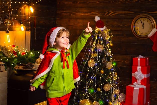 喜びと愛に満ちた家。今年のクリスマス、ご家族の皆様のご多幸をお祈り申し上げます。メリークリスマス、そしてハッピーニューイヤー。かわいい小さな男の子はクリスマスツリーの近くで遊ぶ。子供は家で冬休みを楽しんでいます。