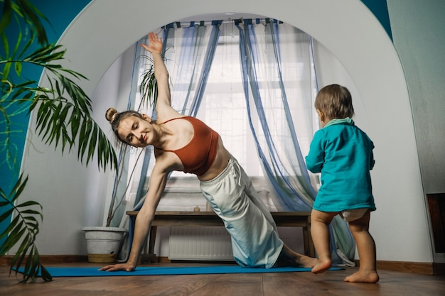 Home fitness workout in new normal pandemic lockdown time yoga at home mother working out practice