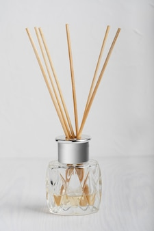 Home fragrance perfume diffuser with wooden sticks in elegant glass bottle on white wooden table