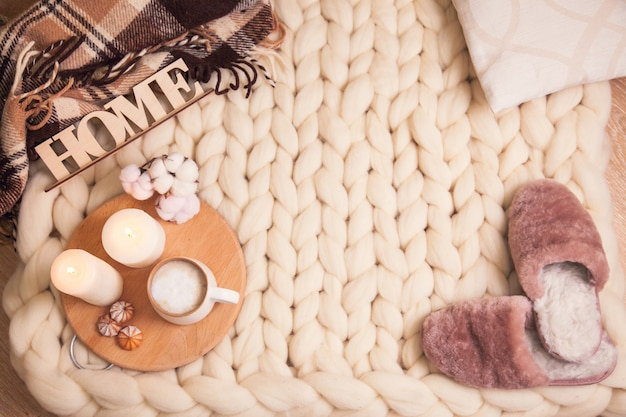 Home fur slippers. cup of cappuccino and cookies, candles, checkered plaid, inscription home on the blanket of thick yarn with copy space. the atmosphere of homeliness and comfort