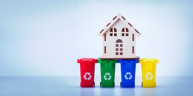 ホームガベージコレクションのコンセプト。コピースペースのある灰色の背景に個別の収集ゴミ用のコンテナで家をモデル化します。バナー。