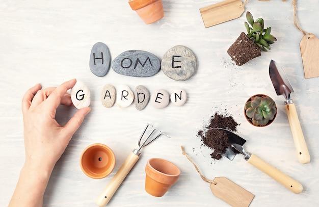 Концепция домашнего садоводства. квартира лежала с текстом мой сад на камнях и садовых инструментах. минимальная композиция вид сверху