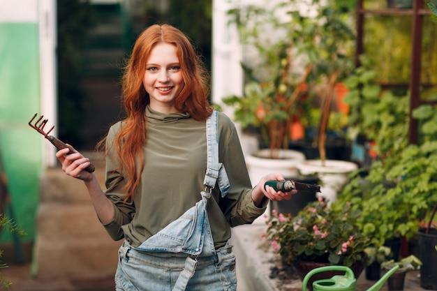 Концепция домашнего садоводства. молодой имбирь агроном женщина в джинсовые комбинезоны и грабли и лопатой посадки растений. весенний дом садового растения.