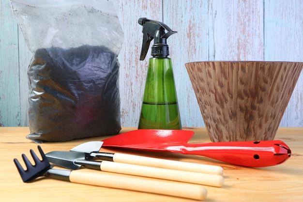 Мини-инструменты для домашнего садоводства с горшком и почвой на столе