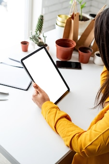 가정 원예. 디자인을 모의합니다. 여자 정원사 손 빈 화면으로 디지털 태블릿을 들고