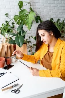 家庭菜園。小規模なビジネス。植物に囲まれたデジタルタブレットに取り組んでいる女性の庭師