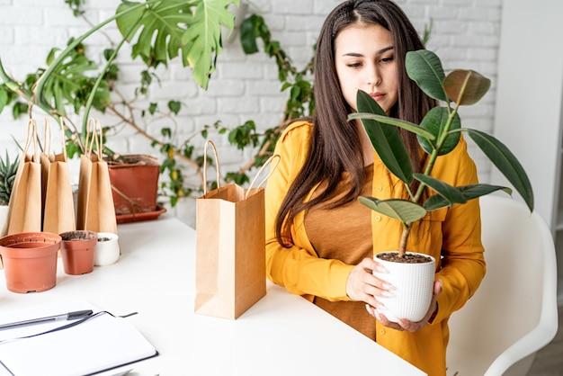 家庭菜園。小規模なビジネス。植木鉢をクラフトバッグに入れて販売する準備ができている植物の世話をしている若い女性の庭師