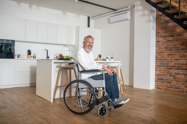 At home. gray-haired mature handicapped man in the kicthen