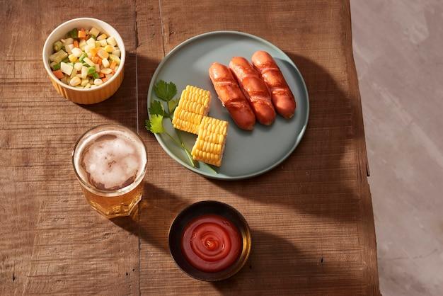 ダークプレートのホームグリルソーセージ、ダーク木製テーブルの肉料理、ホームキッチンのスパイスと塩のホットソーセージ、コピースペース、素朴なスタイル、アート