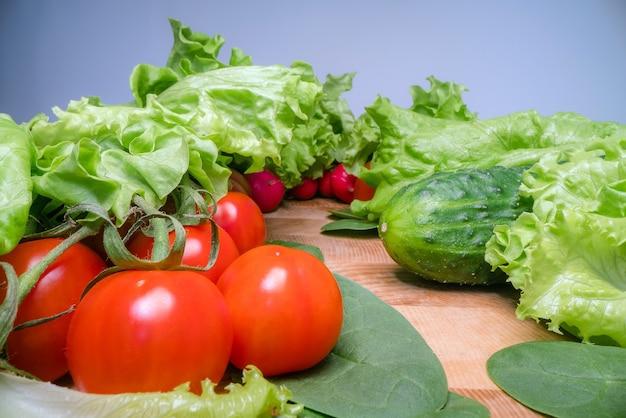 木製のテーブルの背景に自家栽培と収穫野菜。