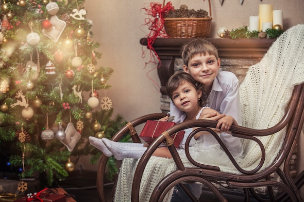 Home a happy boy and girl with boxes of gifts in the christmas interior