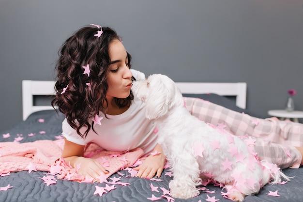 현대 아파트에서 침대에 분홍색 tinsels에 잘라 갈색 곱슬 머리와 잠옷에 젊은 아름 다운 여자의 애완 동물과 함께 홈 행복한 순간. 흰색 작은 강아지와 함께 집에서 놀리는 사랑스러운 예쁜 모델