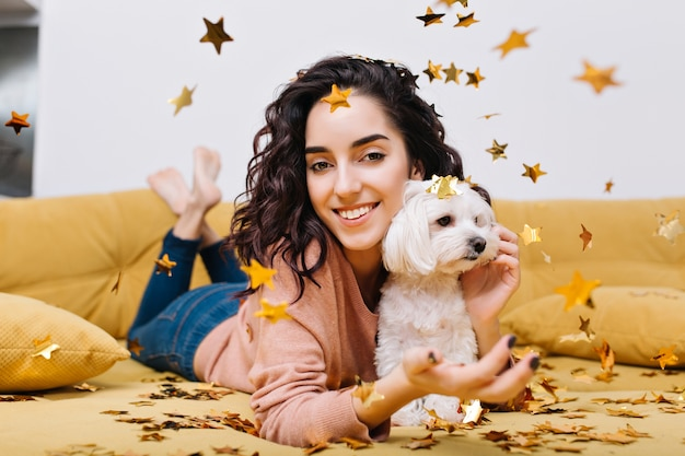 Casa momenti felici con animali domestici di giovane bella donna con capelli ricci castana tagliati divertendosi in orpelli dorati sul divano in appartamento moderno. modello grazioso adorabile che si rilassa a casa con il piccolo cane bianco